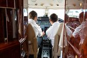 stock photo of cabin crew  - Rear view of pilot and copilot operating controls of private jet - JPG