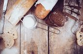 foto of whole-wheat  - White french baguette and fresh rustic loaf of wholemeal rye bread sliced and flour on a wooden board bakers food background - JPG