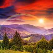 foto of coniferous forest  - rainbow over mountain steep with coniferous forest in evening light - JPG