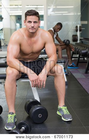 Handsome bodybuilder sitting on bench in weights room at the gym