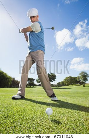 Golfer swinging his club on the course on a sunny day at the golf course
