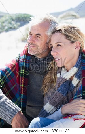 Happy couple wrapped up in blanket sitting on the beach on a bright but cool day
