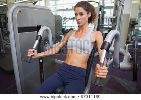 Fit woman using the weights machine for her arms at the gym