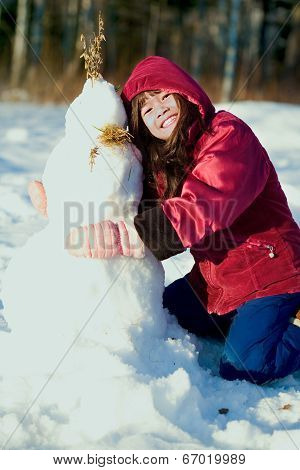Young Girl In Red Jacket Playing Outdoors In Snow