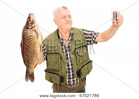 Mature fisherman holding a fish and taking selfie isolated on white background