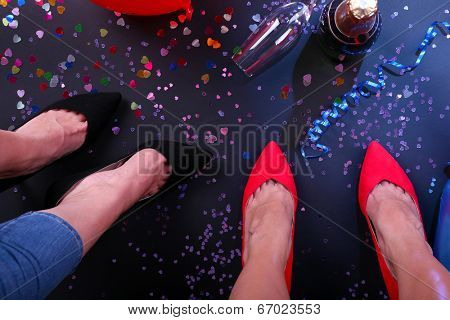 Legs with confetti, champagne and balloons on the floor