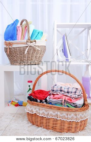 Colorful towels and clothes in baskets, on interior background
