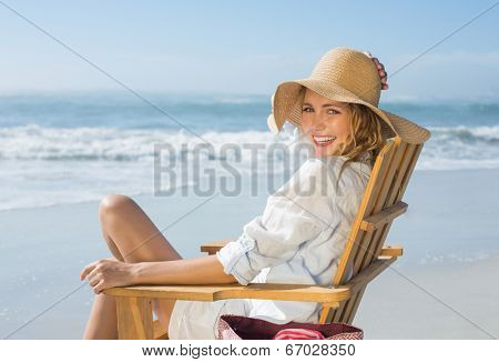 Smiling blonde sitting on wooden deck chair by the sea on a sunny day