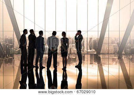 Composite image of business colleagues talking in large room overlooking city