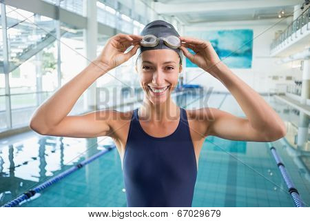 Pretty swimmer standing by the pool smiling at camera at the leisure center