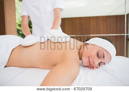 Beauty therapist rubbing womans back with heated mitts in the health spa