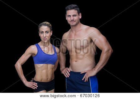 Crossfit couple smiling at camera with hands on hips on black background