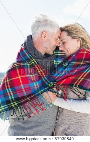 Happy couple wrapped up in blanket standing on the beach on a bright but cool day