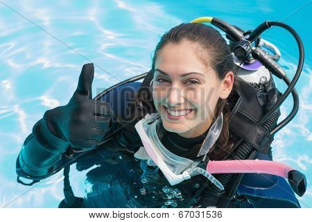 Smiling woman on scuba training in swimming pool showing thumbs up on a sunny day