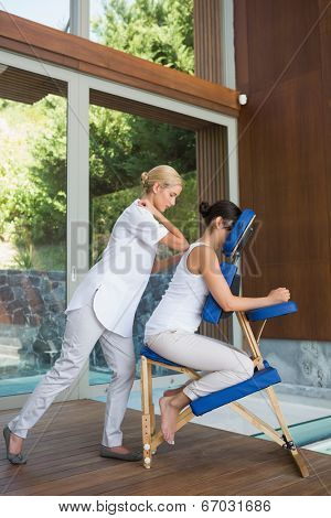 Relaxed brunette getting a massage in chair at the spa