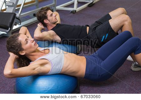 Fit man and woman doing sit ups on exercise ball at the gym