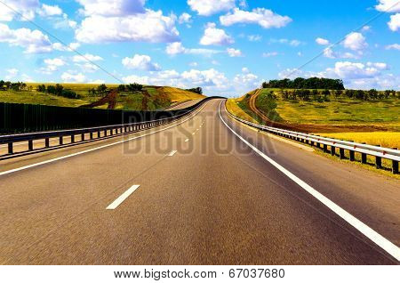 The road through the green fields and clouds on blue sky in hot summer day