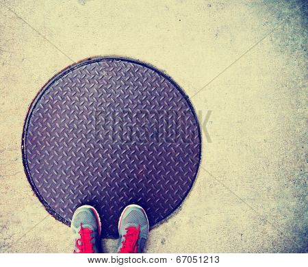 a pair of feet on a manhole cover done with a retro vintage instagram filter
