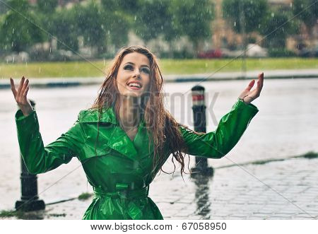 Happy redhead enjoying the rain drops in the park, outdoor shot.