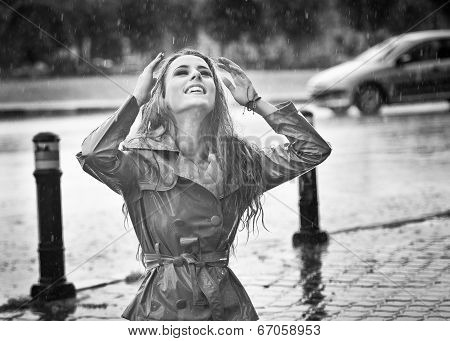 Beautiful woman wearing a coat posing in the rain. Happy long hair girl enjoying the rain drops