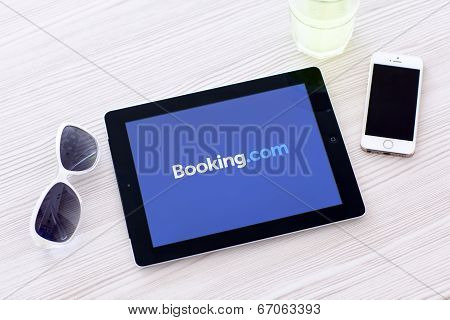 Ipad With App Booking On The Screen Lies On A Table With Glasses And Iphone 5S
