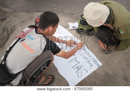 Indonesian Students Write Poster For Pictures On The Top Of Volcano Merapi
