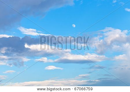 Moon And Grey Clouds In Blue Evening Sky