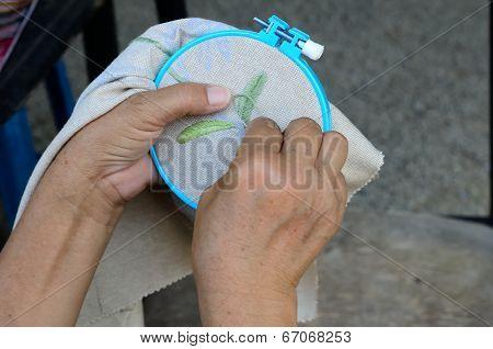 woman hands doing cross-stitch