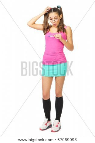 Confused schoolgirl with pregnancy test isolated