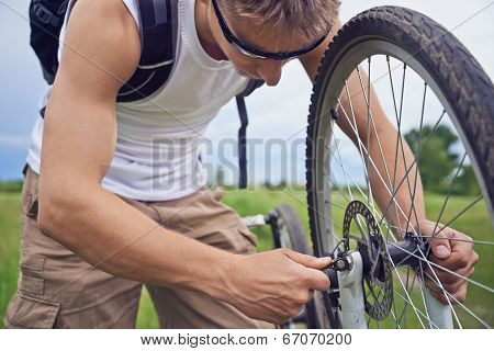 Cyclist Checks Brake Wheel Of Bicycle