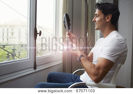 Beautiful man looking at himself in a hand mirror after rejuvenating
