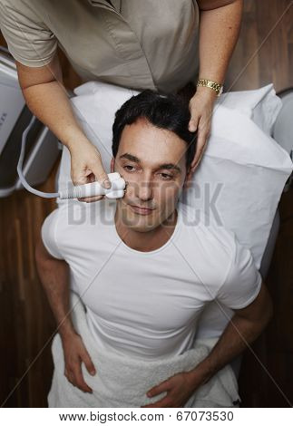 Male patient at facial procedure looking to the doctor