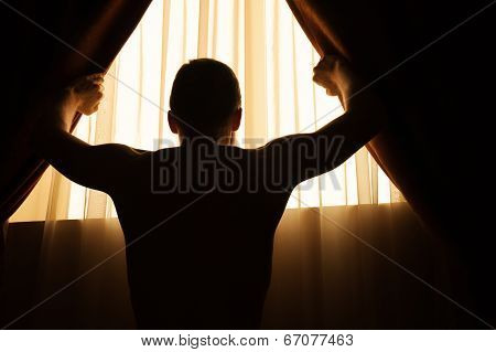 Man In Dark Room Opens Curtains On Window To The Morning Light