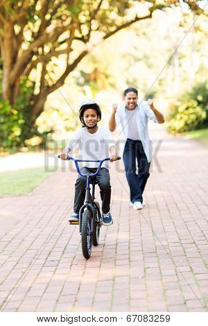 happy father cheering when his son can ride a bike on his own for the first time