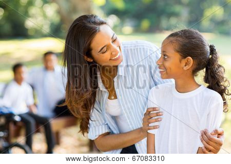 happy indian mother and cute daughter in front of family