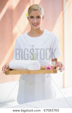 Smiling beauty therapist holding tray of beauty treatments at the spa