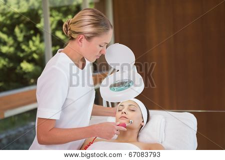 Peaceful brunette getting micro dermabrasion from beauty therapist in the health spa