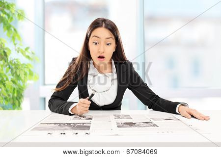 Businesswoman reading the news with scrutiny indoors