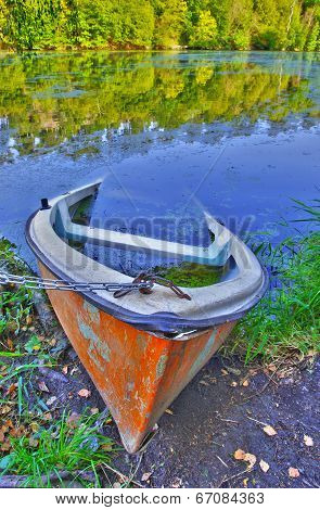 Sinking boat ashore the pond