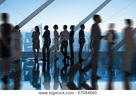 Businessmen talking in large room overlooking city