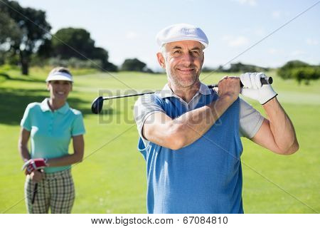 Happy golfer teeing off with partner behind him on a sunny day at the golf course
