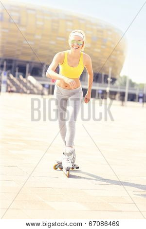 A picture of a happy rollerblader skating in front of the Amber Stadium in Gdansk
