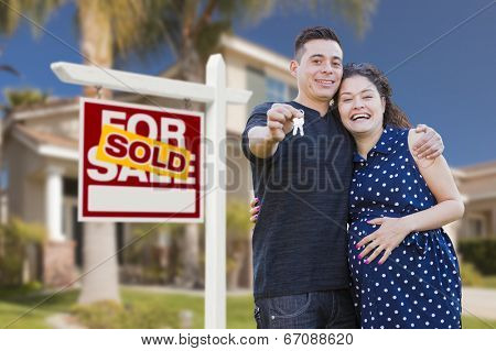 Young Happy Pregnant Hispanic Young Couple with House Keys in Front of Their New Home and Sold For Sale Real Estate Sign.