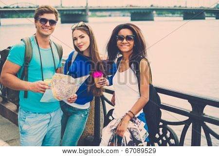 Multi-ethnic friends tourists with map and coffee cups near river in a city