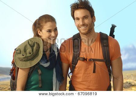 Happy young couple trekking in nice weather.