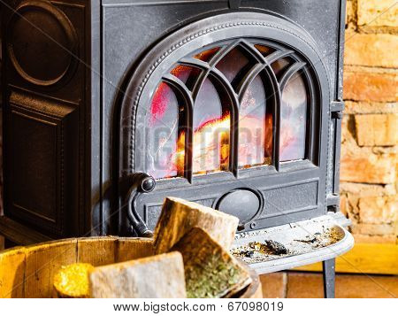 Fireplace With Fire Flame And Firewood In Barrel Interior. Heating.