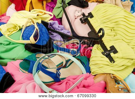 Close up on a big pile of clothes and accessories thrown on the ground.