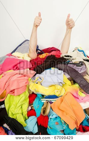 Man hands signing thumbs up reaching out from a big pile of clothes and accessories.