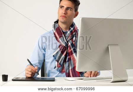 Graphic designer using graphics tablet to do his work at desk