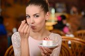 pic of cream cake  - Portrait of young pretty smiling woman eating cake at shopping mall cafe